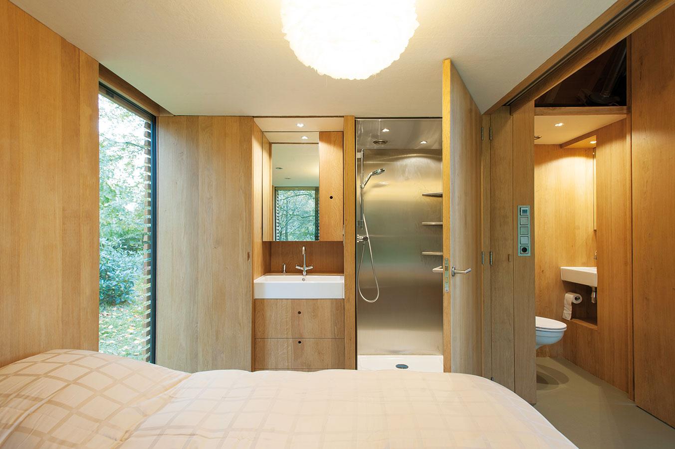 Stěna zdubového dřeva, kterou zdruhé stěny kryje plná břidlicová fasáda, vsobě kromě běžných úložných prostor skrývá také kuchyňskou linku atoaletu, ve spací části pak také jednoduchou koupelnu (umyvadlo asprchový kout). FOTO ROEL VAN NOREL
