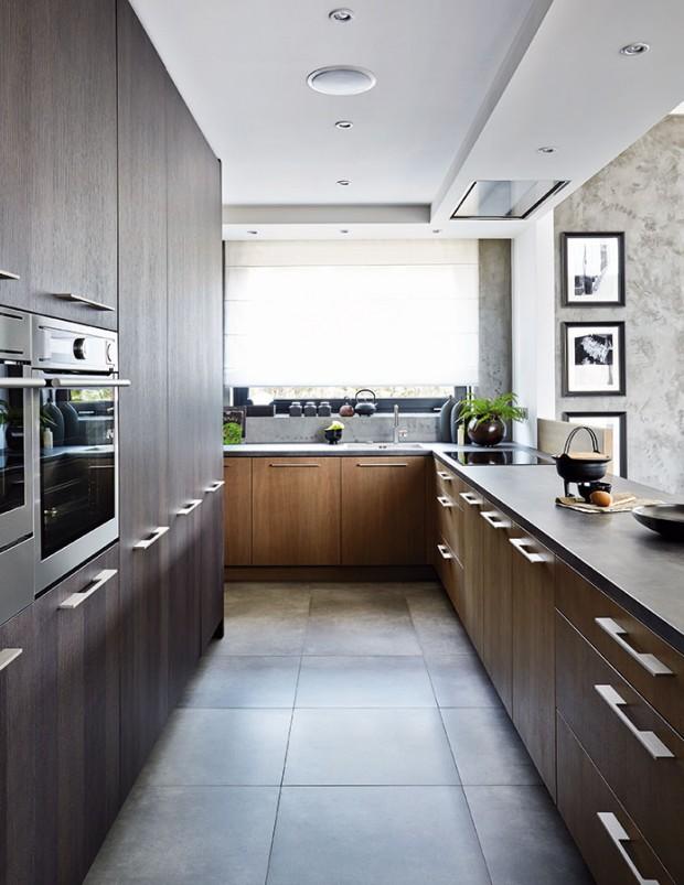 Kuchyňská linka snádherným, hřejivým povrchem mořeného dubu aúchytkami zmatného kovu, osvěžená zelení rostlin, příjemně kontrastuje svelkoformátovou dlažbou imitující beton. FOTO PETR KARŠULÍN