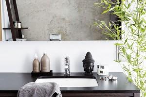 Moderní atrochu chladnou betonovou stěrku zjemňuje tmavý dřevěný nábytek, ataké doplňky arostliny vasijském duchu. FOTO PETR KARŠULÍN