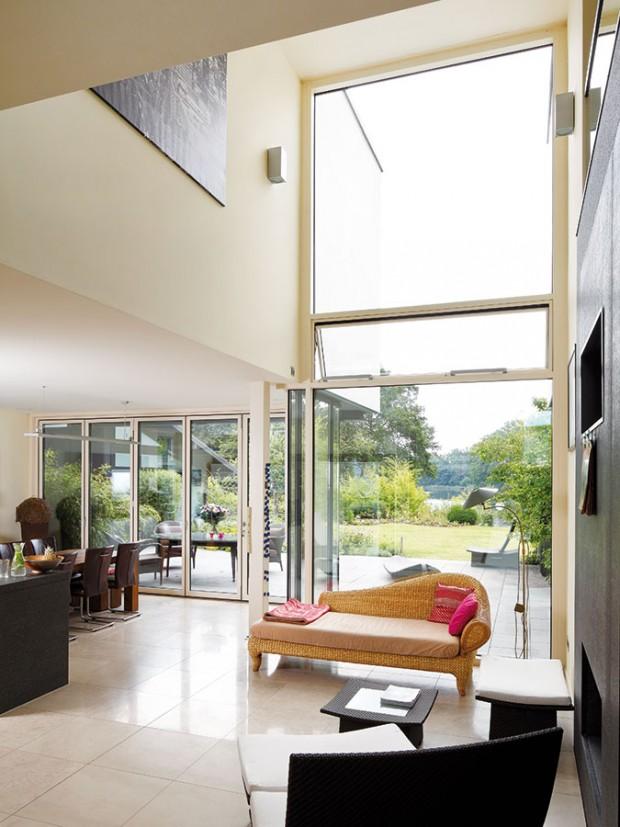 Obývací prostor spřístupem na terasu avýhledem na jezero. Automaticky řízená ven výklopná okna astřešní okna pro příčnou ventilaci vlétě. FOTO SCHÜCO INTERNATIONAL KG