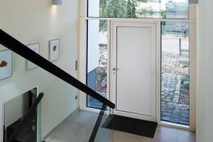 Vstupní dveře scelistvou výplní askrytými panty jsou vybaveny biometrickou kontrolou vstupu přes čtečku otisků prstů. FOTO SCHÜCO INTERNATIONAL KG