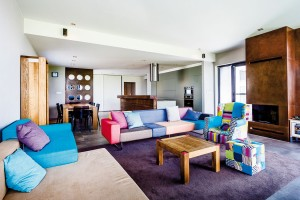 Obývací části dominuje barevná textilní sedačka snápaditým křeslem, jehož veselý design odráží povahu rodiny. Domácí paní plánuje vblízkém čase dotvořit interiér obrazy. FOTO WIENERBERGER