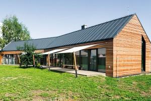 Vdobré formě. Díky tvaru připomínajícímu tradiční stodolu aumístění na pozemku, které respektuje sousední rodinné domy, se novostavba harmonicky začlenila do okolního prostředí. Navíc tak může dům maximálně využívat solární zisky adomácí slunečnou část zahrady. FOTO ERIKA BÁNYAYOVÁ AMARTIN BOLEŠ
