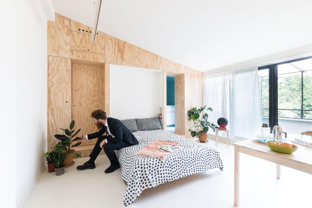 """Dva """"aktivní"""" panely na stěnách ukrývají manželskou postel, posuvné dveře do kuchyně a koupelny, šatnu nebo třeba klimatizační jednotku. Obytný prostor se během dne může několikrát proměnit, zcela podle aktuálních potřeb svých obyvatel."""
