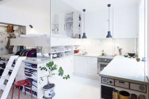 """Konzolové řešení postele zvolila majitelka stockholmské garsonky orozloze 36 m2 jako úsporné apraktické řešení spacího prostoru. Od kuchyňské části lůžko odděluje skleněná stěna, pod lůžkem se našel dostatek místa pro malou """"šatnu"""". FOTO KARIN MATZ"""
