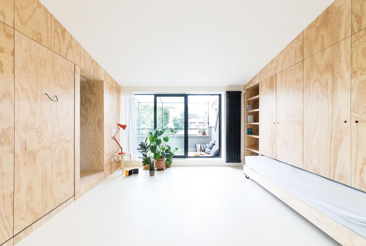 """Díky """"panelovému"""" řešení se architektům podařilo dostat do bytu vše potřebné, přitom však zachovali volný centrální prostor, který se po uzavření panelů stává prostornou jídelnou, tanečním parketem či tělocvičnou."""