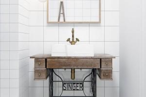"""Dotek vintage. Nádech starých časů dodává koupelně stolek od starého šicího stroje Singer. Tuhle klasiku architekti doplnili novým umyvadlem a retro baterií. Preciznost prokázali tím, že povrch baterie ladí s úchytkami na zásuvkách stolku, sloužících jako milá """"schovka"""" pro drobnou kosmetiku. FOTO INT2ARCHITECTURE"""