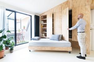 Koupelnu a kuchyni pojali architekti jako dva modré, monochromatické boxy, zatímco obytný prostor je charakteristický kontrastem bílých stěn a dřevěných povrchů.