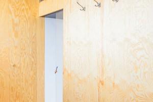Zádveří bytu je obložené překližkou, která se stala hlavním materiálem při jeho zařizování. Sympatickým prvkem je police nad dveřmi vedoucími do hlavní obytné části i zvolené svítidlo. FOTO ALEKSANDRA VAJD
