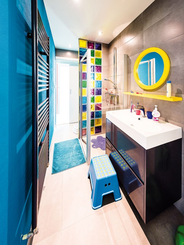 Dětská koupelna jasně ukazuje, kdo je vtéto místnosti doma. Hravá barevnost doplňků apestrá sklobetonová zástěna dětem zpříjemňuje koupací rutinu. FOTO WIENERBERGER