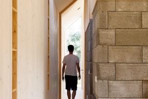 Ulička do ložnice. Vysoké okno na východním konci domu, vložnici rodičů, opticky prodlužuje chodbu ado dlouhého domu vnáší ještě intenzivnější pocit pohybu. FOTO ERIKA BÁNYAYOVÁ AMARTIN BOLEŠ