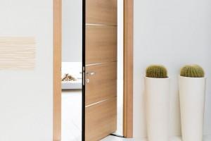 Principem posuvně kyvných dveří je posunutá osa jejich vlastního otáčení. Otáčejí se tak, že křídlo se začne otevírat nejprve jako otočné, ale přibližně v jedné třetině začíná zasahovat do obou dvou prostorů. Tyto dveře potřebují speciálně upravenou zárubeň. FOTO SAPELI