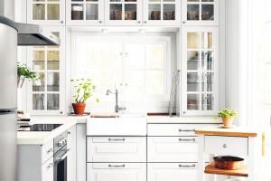 Ideální kuchyně do malého prostoru. Jak by měla vypadat? Světlá, s maximálním využitím stěn pro úložné prostory. Prosklená dvířka umožňují snadnou orientaci ve skříňkách, zabraňují však nadměrnému usazování prachu a tím výrazně usnadňují údržbu. FOTO IKEA