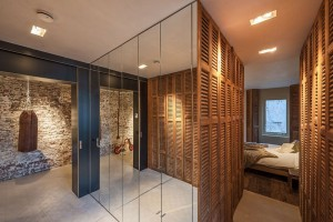 Stěna pokrytá zrcadly poblíž ložnice ukrývá úložný prostor. Foto: Teo Krijgsman
