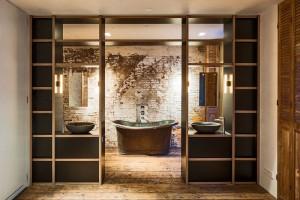 Při pohledu z ložnice vypadá koupelna velmi symetricky a skutečně industriální. Je tomu tak díky surové stěně, která je ponechána za velkou kovovou vanou. Foto: Teo Krijgsman