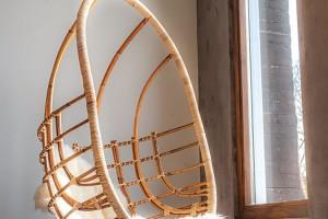 Jedním z přidaných dřevěných designových doplňků je visící křeslo – houpačka, z níž je možné přes velké okno pozorovat okolní svět. Foto: Teo Krijgsman