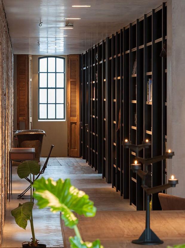 Skutečně netradičně – přímo na chodbě – se nachází minimalistická koupelna, která je prostřednictvím knihovních polic propojená s ložnicí. Foto: Teo Krijgsman