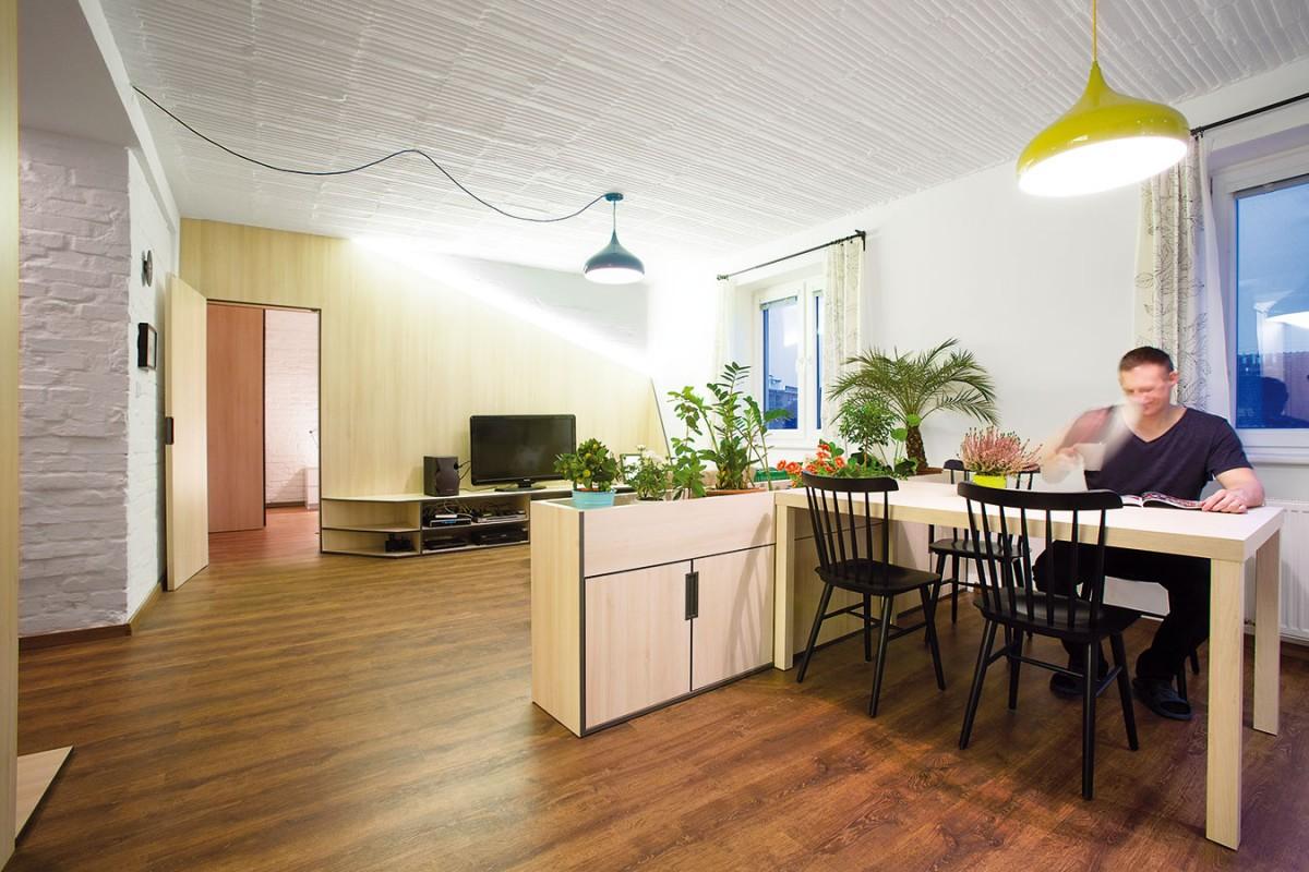 """Dveře skryté vdřevěném obkladu vedou do ložnice. Světlé dřevo zvolili architekti jako mezistupeň mezi tmavou """"pánskou"""" podlahou abílými povrchy stěn istropu. FOTO TOMÁŠ MANINA"""