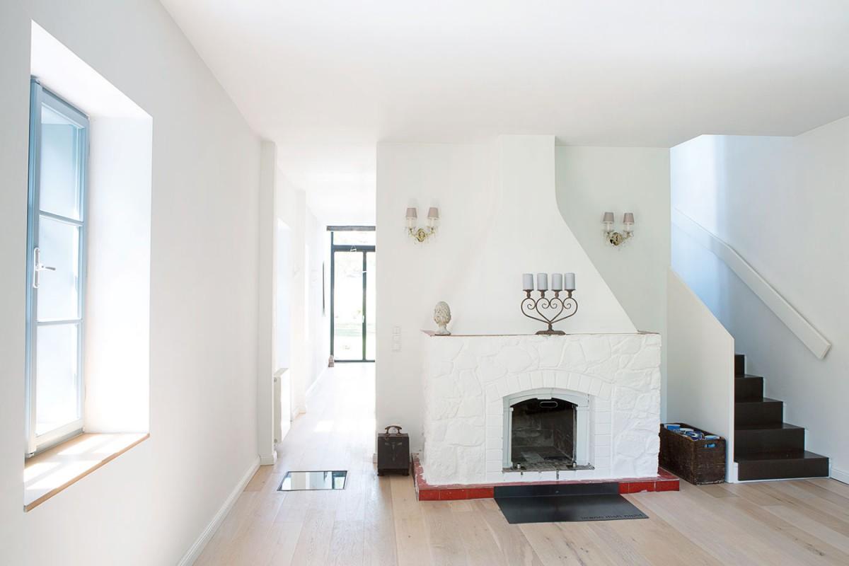 Dominantou obývacího pokoje je velký zděný krb, který je tradičním apřirozeným centrem domácnosti. Kolem něj se zjedné strany přechází do kuchyně sjídelnou, zdruhé se po dřevěném schodišti vychází do podkroví – idíky řešení sminimem dveří vypadá přízemí otevřeně acelistvě. FOTO VELUX