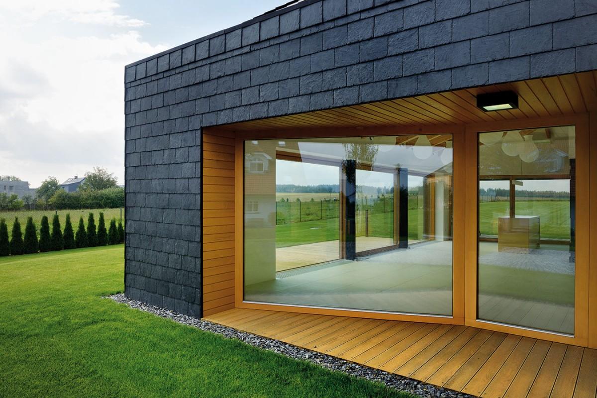 Kombinace dubového dřeva abřidlice je zestetického hlediska velmi efektní. Celkově tento dům díkypoužitým přírodním materiálům acitlivému zasazení působí vkrajině velmi příjemně. FOTO ROMAN POLÁŠEK