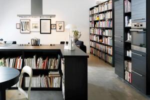 Pro knihomoly. Jedním ze způsobů, jak udělat zkuchyně obývací pokoj, je využít knihy. Všude. Těch pár polic sdózami se při takovém množství literatury zcela ztratí. Důležité je však mít přehled. FOTO IKEA