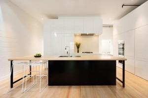 Ostrost černo-bílé kombinace zjemňuje použití přírodních materiálů, konkrétně dřeva, na plochy podlah apracovních desek. Černá naopak vnáší do celé kompozice kuchyňského prostoru vzruch ašarm. FOTO Ben Hosking (techne.com.au)