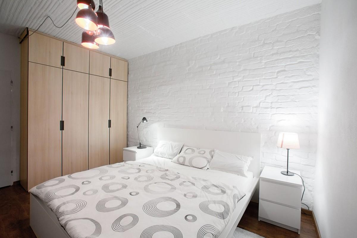 Nábytek na míru vdřevěném dekoru je odlišený od typového. Ten je vpřípadě ložnice jednoduchý bílý, vystihující pánskou ležérní eleganci. FOTO TOMÁŠ MANINA