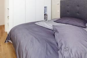 Ložnici rodičů dominuje pohodlná postel sčalouněným čelem, které prostor příjemně změkčuje. Jednolitou plochu vestavných skříní nápaditě ozvláštňují otevřené niky. FOTO Lubor Sladký