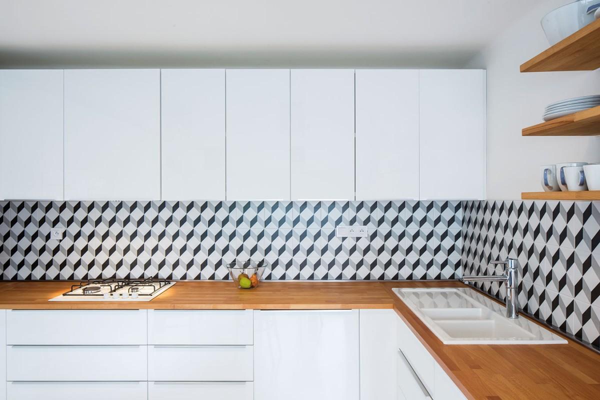 Jednoduchou anadčasovou kombinaci bílých kuchyňských skříněk apracovní desky zpřírodního dřeva ozvláštňuje jemný černo-bílý dekor za linkou. foto tomáš brabec