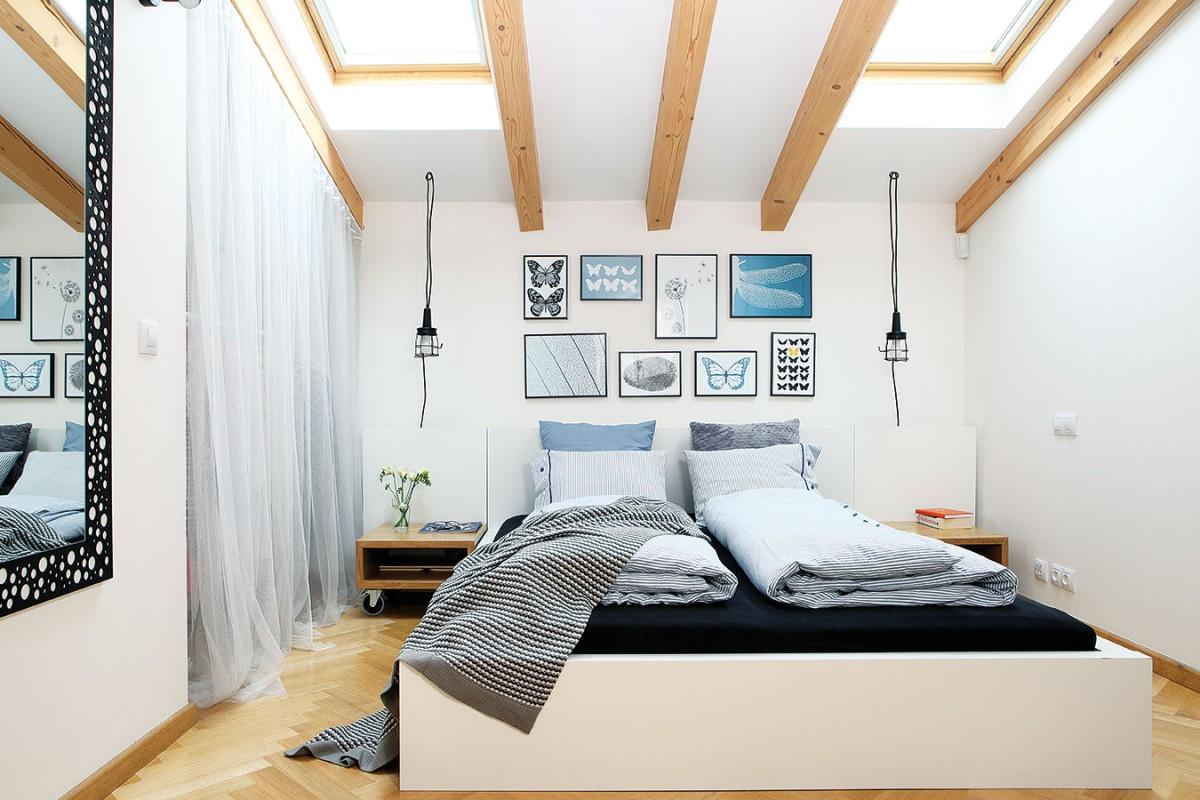 Vjemně působící ložnici doplňuje základní paletu bílé, černé aodstínů dřeva uklidňující modrá. Příjemným akcentem jsou ze šikminy visící svítidla nahrazující standardní stolní lampy. Za poloprůhledným síťovým závěsem se ukrývá šatník. FOTO ROBERT ŽÁKOVIČ