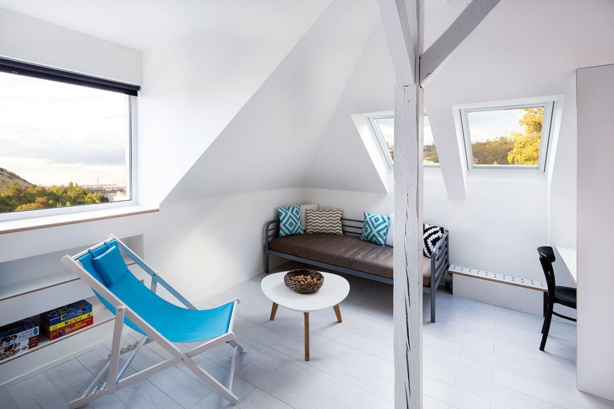 Obývací kout si dopřává barev nejen vpodobě doplňků, ale idíky velkorysým výhledům na okolí. Umístění pod šikminou mu dodává na pocitu útulnosti. foto tomáš brabec
