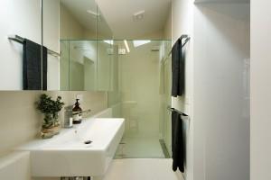 Jednoduchou bílou barevnost vkoupelně doplňují zrcadlové askleněné plochy. Prostor opticky zvětšují adodávají mu lesk. FOTO Ben Hosking (techne.com.au)