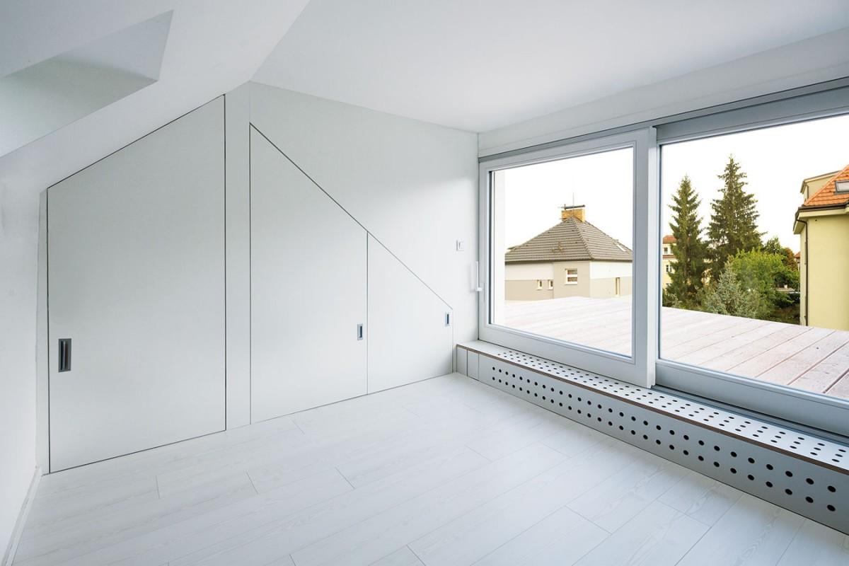 """Kumšt spočívá vkombinaci. Nadčasově laděný interiér vminimalistickém duchu tvoří jednoduchý nábytek vbarvách bílé apřírodního dřeva. Kontrastní barvou se tu stala černá, sem tam se vinteriéru objevuje """"koření"""" vpodobě několika barevných detailů. foto tomáš brabec"""