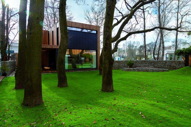 Prostorná travnatá zahrada odděluje dům mladých od domu rodičů. Tak si tyto dva domy vybudovaly užší vztah a mírně se oddělily od ostatních.