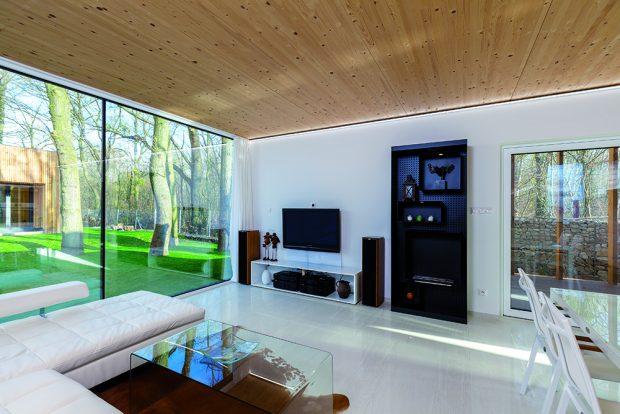 Dřevěný strop působí jako barevný i materiálový protipól k bílé podlaze z umělého kamene. Interiér tak získal teplejší vzhled.
