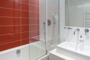 ednoduchou koupelnu oživuje červený obklad za vanou. Podobně jako vkuchyni za linkou, kde mu pan majitel původně nemohl přijít na chuť. FOTO TOMÁŠ BRABEC