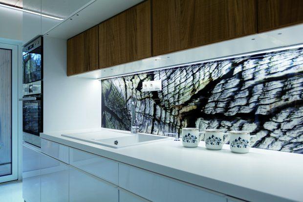Kuchyňská zástěna je odkazem na prostředí, ve kterém se dům nachází. Se stromy za oknem je tak interiér a exteriér propojen dokonale.