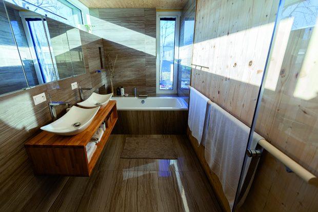 Koupelna orientovaná na východ a jih je téměř celý den prosvětlená přirozeným světlem. Netradiční rozměry a umístění oken jí navíc dodávají jakousi poetickou dynamiku.