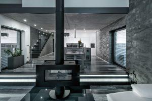 Největší plocha vpřízemí je vyčleněna pro halu sobývákem, kuchyní ajídelnou vjednom. Celému prostoru dominuje azároveň pomyslně dělí obývací akuchyňskou část oboustranný designový krb. FOTO Tomáš Vejrosta, Inoutic