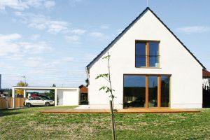 Štítový dům se sedlovou střechou je doplněn jednoduchým garážovým stáním, odděleným od hlavního objektu. FOTO Jan Medek, Jakub Tomec
