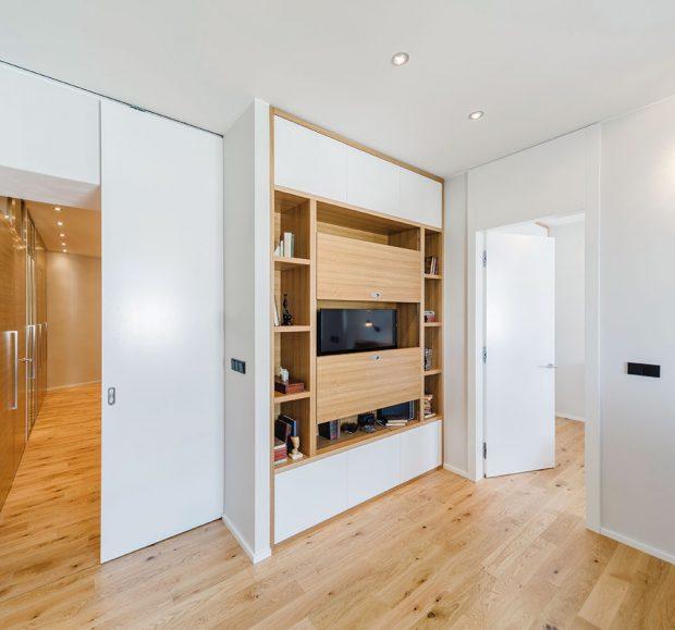 Základem vzhledu celého bytu je kvalitní přírodní dubová podlaha, interiér je vybaven zejména bílým lakovaným nábytkem sdýhovanými prvky. Vše opět laděno tak, aby vynikly předměty vpolicích. FOTO ARCHIV DELICODE