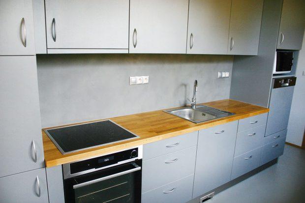 Přírodní deska šedé kuchyně opět koresponduje sdalšími dřevěnými detaily vinteriéru. FOTO Jan Medek, Jakub Tomec