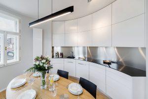Obdivuhodná je vestavěná oblouková kuchyňská linka zohýbaných lakovaných desek aumělého kamene. Vhodnou volbou pro jídelní část místnosti byl oválný stůl umístěný na střed.FOTO ARCHIV DELICODE