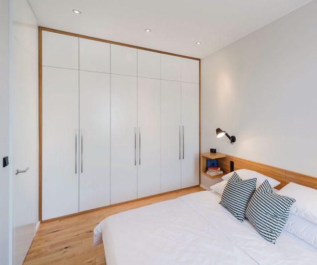 Bílý nábytek na míru sdýhovanými prvky je použit ve všech prostorách bytu, ložnici nevyjímaje. Zde je však kladen velký důraz na praktičnost amaximální objem úložných prostor. FOTO ARCHIV DELICODE