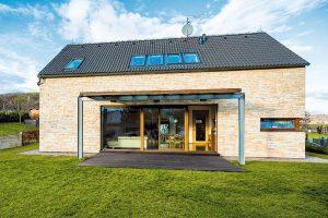 Jednoduché linie, promyšlené detaily. Jednoduchý dům, který tvarem ideálně zapadá do venkovského prostředí, ozvláštňuje působivá fasáda zpískovce aněkolik funkčních prvků, především promyšleně umístěná okna azastřešená terasa. Foto VELUX