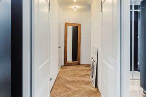 Posuvné dveře sdekorativními kazetovými prvky avýrazným kováním, díky nimž působí chodba mimořádně vzdušně, byly vyrobeny na míru. Vtémže duchu se nese iobložení stěn, které bylo vminulosti jedním zcharakteristických znaků starých měšťanských domů. FOTO TOMÁŠ MALÝ