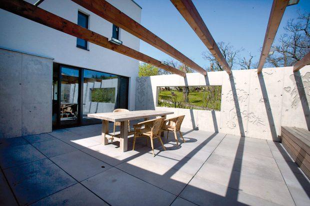 Severní terasa či spíše patio chráněné stěnami z grafického betonu poskytuje v létě příjemný stín. Dřevěná konstrukce nad terasou je naplánována jako opora pro vistárii, která tu časem vytvoří ještě příjemnější mikroklima. Foto ITB Development