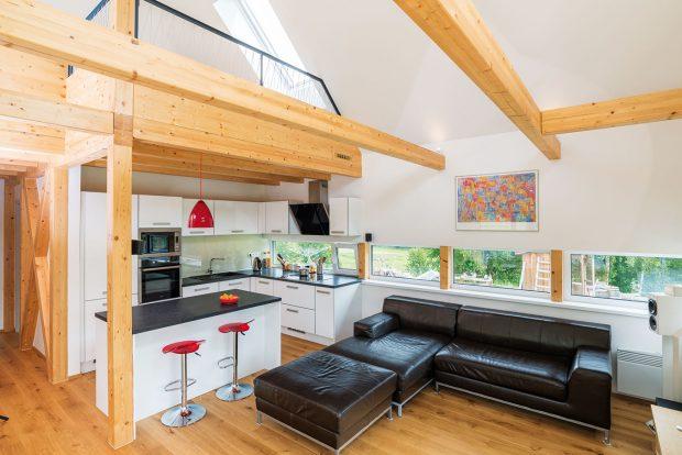 Interiér je zařízen jednoduše a účelně – významným prvkem je přiznané dřevo trámové konstrukce i podlah. FOTO MARTIN ZEMAN