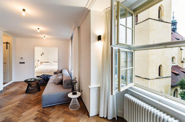 Téměř všechny zařizovací prvky v interiéru byly podle návrhů architektů vyrobeny na míru. Výjimkou není ani světle šedá rohová sedačka v obývací části. FOTO TOMÁŠ MALÝ