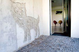 """Před vstupními dveřmi. Architekt se nechtěl na uliční fasádě uchýlit k obligátnímu pohledovému betonu, a tak oslovil výtvarníka Petra Barinku a nechal mu při jejím ztvárnění volnou ruku. """"Je to možná neobvyklé, ale podle mne příjemné. Tyto naivní obrázky dokázaly jaksi """"obrousit hrany"""" a najít specifický způsob komunikace domu s okolím,"""" konstatuje Igor Lichý. Foto ITB Development"""
